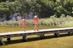 走在湖的一座木脚桥梁的男孩 免版税图库摄影