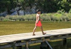 走在湖的一座木脚桥梁的男孩 免版税库存图片