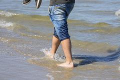 走在湿沙子的一个人的腿由波罗的海,赤足 免版税库存照片