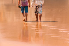走在湿沙子的两个人 免版税库存照片