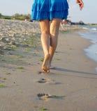 走在湿沙子的赤足妇女 免版税库存照片