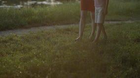 走在湿草的妈妈和儿子 腿在露水,太阳断裂的光芒跨步通过树分支  慢的行动 股票录像