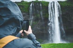 走在瀑布下的远足者妇女在冰岛 免版税图库摄影
