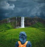 走在瀑布下的远足者妇女在冰岛 免版税库存图片