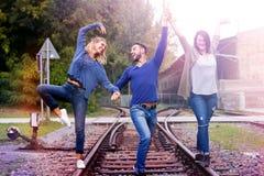 走在火车轨道的三个朋友获得乐趣 免版税库存图片
