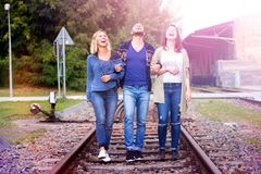 走在火车轨道的三个朋友 免版税图库摄影