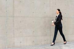 走在灰色墙壁上的确信的企业夫人 免版税图库摄影