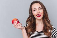 走在灰色墙壁和拿着苹果的愉快的小姐 库存图片