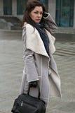 走在灰色外套的街道上的女孩 免版税图库摄影