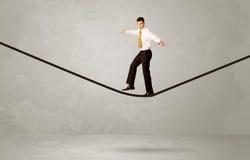 走在灰色空间的绳索的推销员 免版税图库摄影