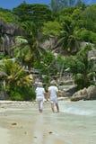 走在热带海滩的愉快的年长夫妇画象  免版税库存图片