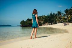 走在热带海滩的少妇 库存图片