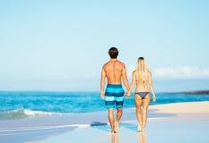 走在热带海滩的有吸引力的夫妇 库存图片