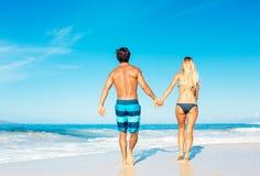 走在热带海滩的有吸引力的夫妇 免版税库存图片