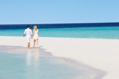 走在热带海滩的浪漫夫妇背面图  免版税库存图片
