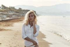 走在热带海滩的肉欲的白肤金发的夫人 库存图片