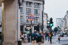 走在牛津街道上的人们在入口附近到牛津马戏地铁车站,伦敦,英国 免版税库存照片