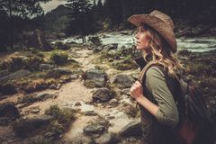 走在狂放的山河附近的妇女远足者 库存照片