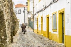 走在狭窄的街道上的老妇人在古老罗马aqu之间 免版税图库摄影