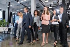 走在现代办公室、确信的商人和女实业家的全长商人队衣服的不同与 免版税库存图片