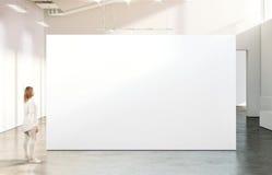 走在现代画廊的空白的白色墙壁大模型附近的妇女 免版税库存图片