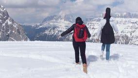 走在白云岩的雪的两年轻女人与大背包和吉他 股票视频