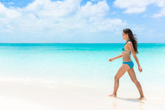 走在白色沙子海滩的美丽的比基尼泳装妇女 免版税库存图片