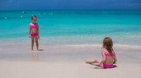 走在白色海滩的小逗人喜爱的女孩在期间 免版税库存图片