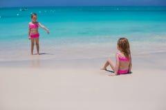 走在白色海滩的小逗人喜爱的女孩在期间 免版税库存照片