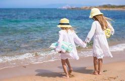 走在白色海滩的小逗人喜爱的女孩在期间 库存图片