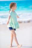 走在白色海滩的愉快的可爱的小女孩 免版税库存照片