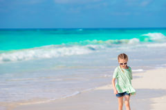 走在白色海滩的愉快的小女孩 免版税库存照片