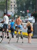 走在的街道上的青年人跳跃的高跷 免版税库存图片