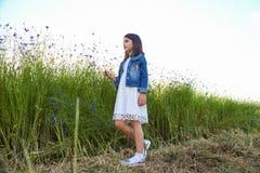 走在矢车菊美丽的蓝色花的领域的女孩  免版税库存图片