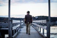 走在码头的中间年迈的白种人人戴从后面和一顶高顶丝质礼帽射击的燃烧物 免版税图库摄影