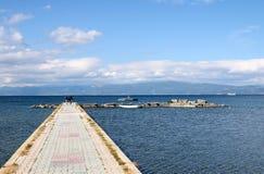 走在码头Ohrid湖的母亲和女儿 免版税库存图片