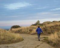走在砂岩岩石和干草中的土道路的妇女 免版税库存照片
