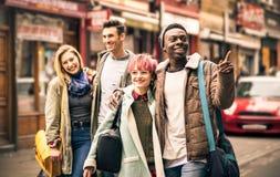走在砖车道的愉快的多种族朋友在Shoreditch 免版税库存图片