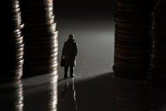 走在硬币堆之间的微型商人 库存照片