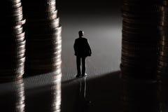 走在硬币堆之间的微型商人 免版税库存照片