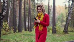 走在秋天公园和发短信给在一个手机的女孩一则消息 股票录像