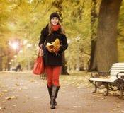 走在秋天公园的一名年轻深色的妇女 图库摄影