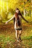 走在秋天公园的女孩 库存照片