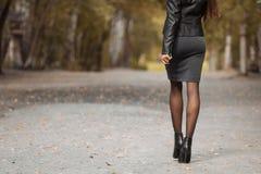 走在秋天公园的女孩 免版税库存照片