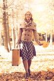 走在秋天公园的少妇 免版税库存图片