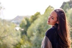 走在秋天公园的年轻愉快的微笑的妇女 免版税库存图片