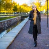 走在秋天公园的愉快的可爱的妇女 免版税库存照片