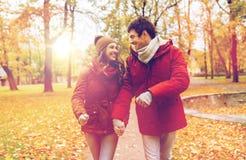 走在秋天公园的愉快的年轻夫妇 免版税库存照片