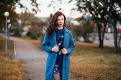 走在秋天公园的时兴的年轻卷曲妇女穿蓝色外套 免版税图库摄影
