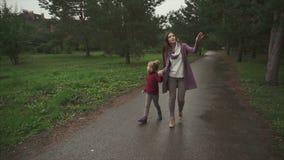 走在秋天公园的母亲和女儿他们互相显示某事 影视素材